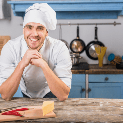 Smiling chef with food on chopping board in kitchen